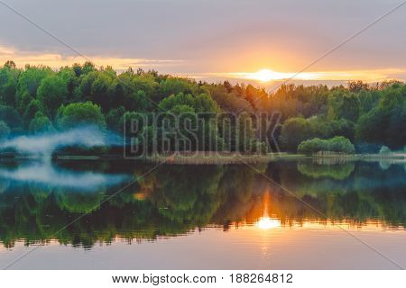 A calm sunset on the shore of the lake where the forest reflects in calm water with haze and fog.