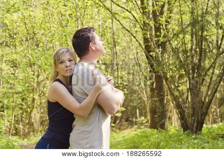 Woman hugs a man who is standing with her back to her. The concept of family problems forgiveness.