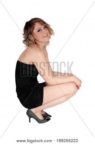 A beautiful young Caucasian woman crouching on the floor in a short black dress isolated for white background.