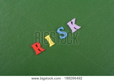 RISK word on green background composed from colorful abc alphabet block wooden letters, copy space for ad text. Learning english concept