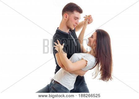 a young man holds girlfriend and tips it in dance close-up isolated on white background