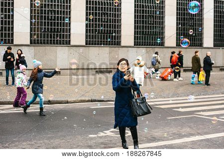 Prague, Czech Republic, December 24, 2016: Asian girl tourist on the phone photographed street show with soap bubbles. Children catch soap bubbles in the background. Entertainment of tourists in Christmas Europe.