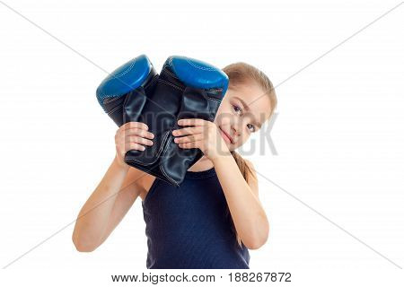little girl after boxing practicing with gloves in hands looking at the camera isolated on white background
