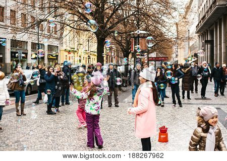 Prague, Czech Republic, December 24, 2016: Children catch soap bubbles. Tourists watch the performance on the street in Prague. Entertainment of tourists in Christmas Europe.