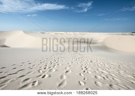 Traces of tourists leading through the sand dunes with blue and green lagoons in Lencois Maranhenses National Park Brazil