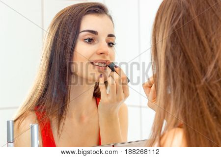 young beautiful girl in a red vest makes lips with lipstick in the bathroom