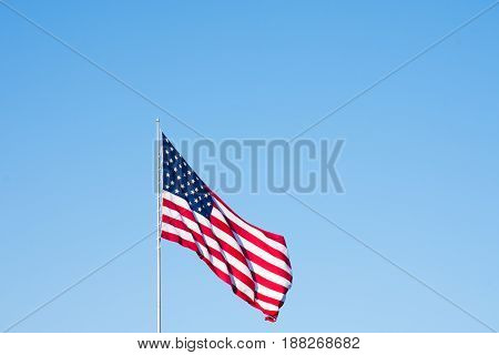 American flag unfurled in the breeze against a medium blue cloudless sky. Image has copy space.