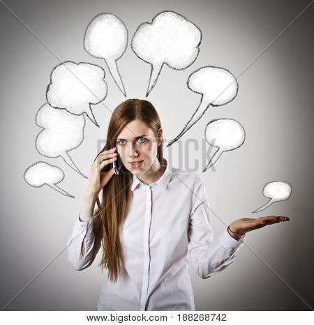 Woman in white is using a mobile phone with blank speech bubbles over her head. Angry woman.