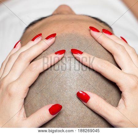 female hand on the man's bald head .
