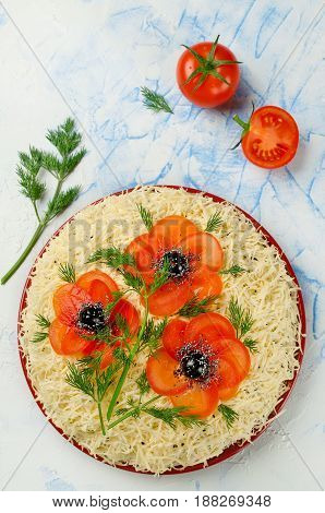 Festive salad sprinkled with grated cheese and decorated with poppies made of sliced tomatoes and olives. Art-food