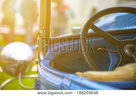 Part of the steering of an old car at sunset with a shallow depth of field
