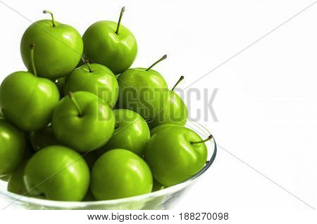 Green sour plums in the plate, plum pictures on the white ground, Quality and natural life-giving green sour plums
