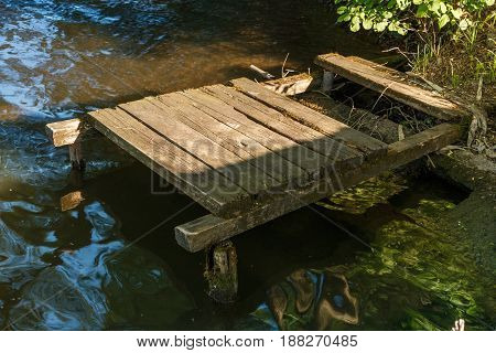 Old wooden pier. Old dilapidated pier. River bank. Russia.