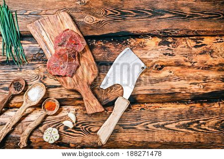 Raw beaf steaks on wooden cutting board. Burned rustic wood background with spices. Top view