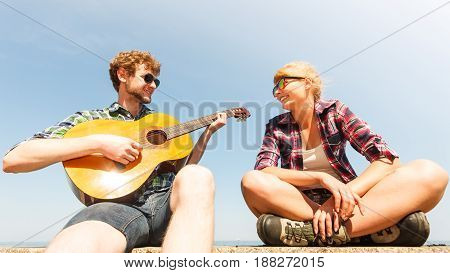 Happy young man hipster playing guitar for woman. Handsome guy and pretty girl in sunglasses relaxing on summer vacation.