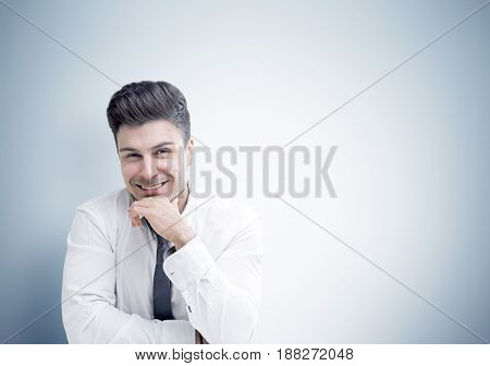 Portrait of a smiling young businessman with light hair and stubble sitting in a white shirt and a gray tie near a gray wall and looking at the viewer. Mock up