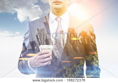 Close up of a young businessman with a paper cup of coffee standing against a blue sky with shining sun. There is a cityscape in the foreground. Toned image double exposure black and white