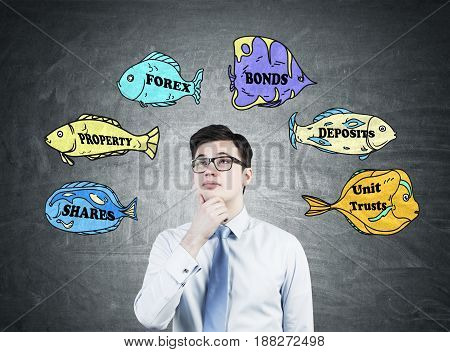Pensive businessman wearing glasses and a white shirt with a tie is standing near a blackboard with business buzzwords written on fish of different colors.