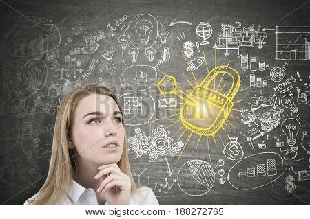 Close up of a pensive blond businesswoman standing near a blackboard with a business scheme a key and a lock sketch on it.
