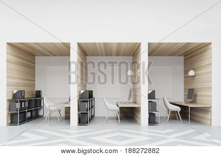 Office cubicles in an office with white and wooden walls. There are blank vertical pictures in each of them a desk with a computer a chair and shelves. 3d rendering mock up