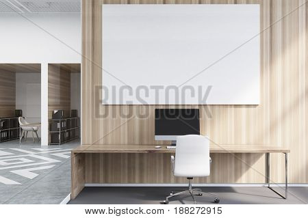 Office cubicles in an office with white and wooden walls. There is a blank horizontal picture a desk with a computer and a chair. Front view. 3d rendering mock up