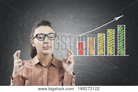 Portrait of a young businesswoman in glasses standing with crossed fingers near a blackboard with a growing graph on it