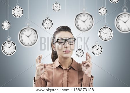 Portrait of a young businesswoman in glasses standing with crossed fingers near a gray wall with lots of clocks around her