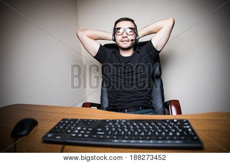 Leasure Young Man With Headphones Playing Computer Games In Dark Room