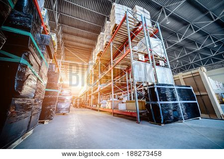 Warehouse industrial and logistics companies. Long shelves with a variety of boxes and containers. Toning the image. Bright sunlight.