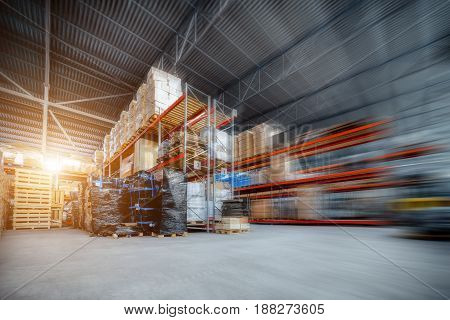 Large hangar warehouse industrial and logistics companies. Warehousing on the floor and called the high shelves. Toning the image. Motion blur effect. Bright sunlight.