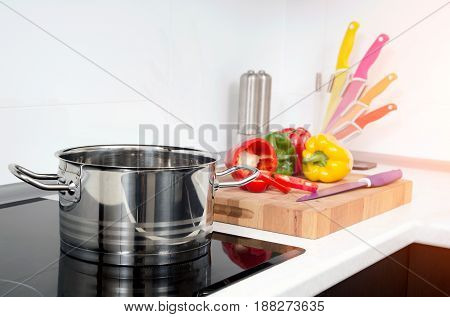 Pot and vegetables in modern kitchen with induction stove. stove cooker hob kitchen pot pan steel gourmet concept