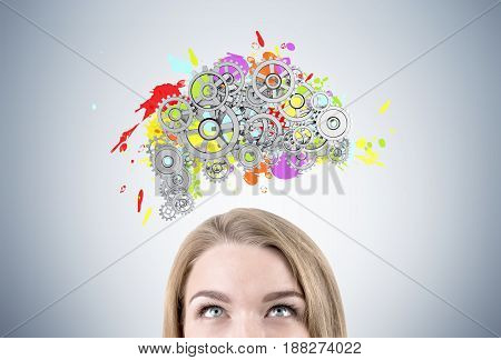 Close up of a head of a blond woman standing near a gray wall with a colored brain shape and gears on top of it.
