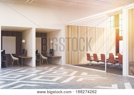 Office cubicles in an office with white and wooden walls. There are blank vertical pictures in each of them a desk with a computer a chair and shelves. Side view. 3d rendering mock up toned image