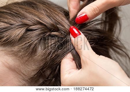 braided pigtails in the beauty salon . A photo