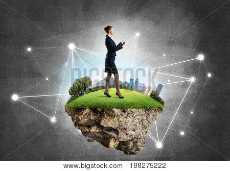 Elegant businesswoman on flying green island against concrete background