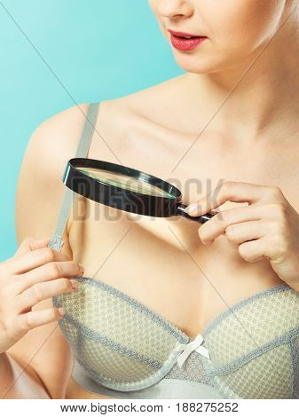 Woman Using Magnifying Glass To Examine Her Moles Skin