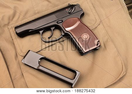 Pistol And Clip. A Pistol In The Background Of A Jacket.