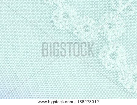 Vintage textile background - fragment of white lace fabric with a floral pattern on a light turquoise background closeup. Selective soft focus.