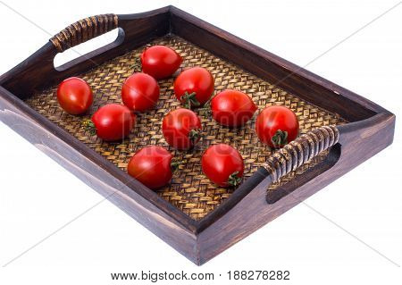 Brown wooden tray with small red tomatoes. Studio Photo