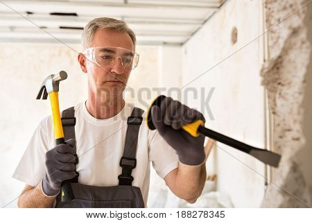 Senior Worker Demolish Wall