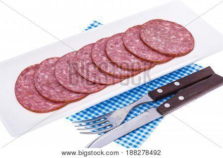 Slices of salami on white plate. Studio Photo