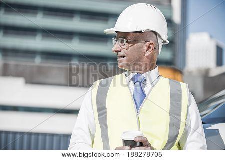 Senior engineer man in suit and helmet outdoor having coffee