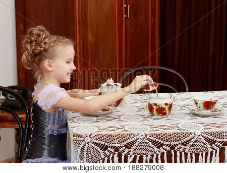 Beautiful little girl Princess , sitting at an antique table with a lace tablecloth and drinking tea.