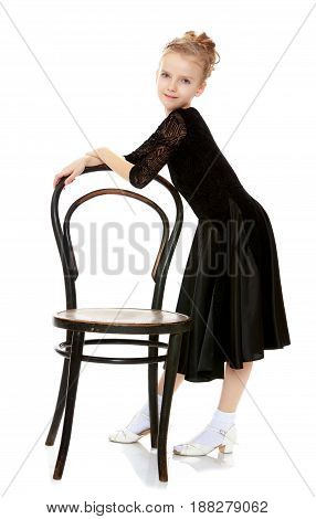 The slender little blonde girl dancer in the long dress of black color made specifically for performing .A girl stands near the old Vienna chair and holds his back with his hands.Isolated.background.