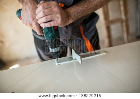 Worker Repairs The Door In A Carpenter's Workshop