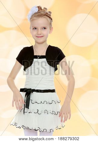 Beautiful little blonde girl dressed in a white short dress with black sleeves and a black belt.Girl poses for the camera.