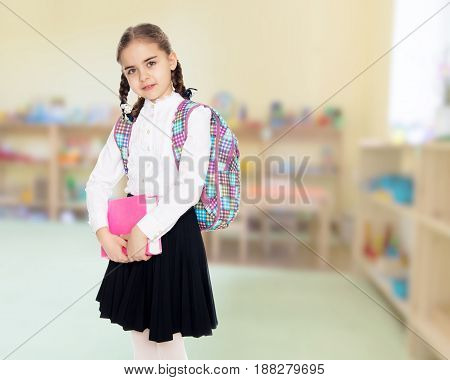 Beautiful little blond schoolgirl, with long neatly braided pigtails. In a white blouse and a long dark skirt.She holds the book in her hands.In the Montessori Room the children's garden.