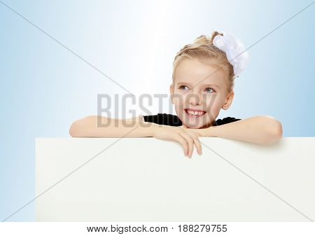 Beautiful little blonde girl dressed in a white short dress with black sleeves and a black belt.The girl peeks out from behind white banner.On the pale blue background.