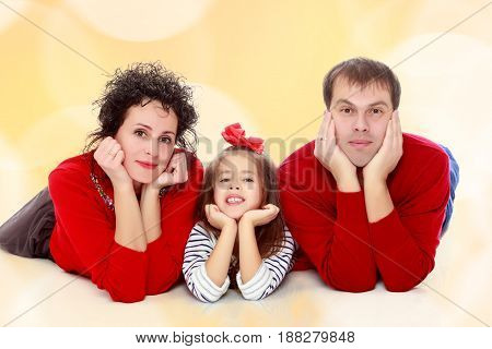 Happy young family dad mom and a little girl in bright red outfits . Family lying on the floor leaning on his hands.Brown festive, Christmas background with white snowflakes, circles.