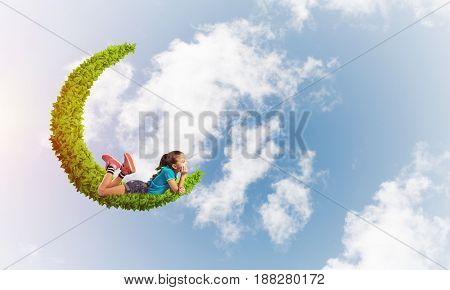 Cute kid girl on green moon floating in day sky